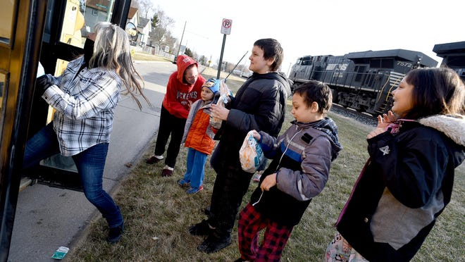 Monroe Public Schools bus driver Martha Ireland retrieves a breakfast bag for Heather Goree of Monroe and her children, Charlie, 6; William, 12; Carter, 8; Elizabeth, 9; and not pictured, Joshua, 11, on the first day of meal delivery in response to the coronavirus pandemic on March 15. MPS is offering remote, cohort or virtual learning plans for the 2020-21 school year to continue to slow the spread of COVID-19.
