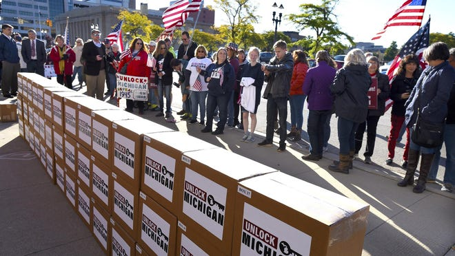 A group gathers as boxes filled with petition signatures are delivered by Unlock Michigan to the Michigan Department of State Bureau of Elections in Lansing, Mich., Friday, Oct. 2, 2020. The Michigan group on Friday submitted at least 539,000 signatures in a bid to repeal a law that has given Gov. Gretchen Whitmer broad emergency powers during the coronavirus pandemic, demanding that the veto-proof initiative be put before the Republican-led Legislature before the year's end.