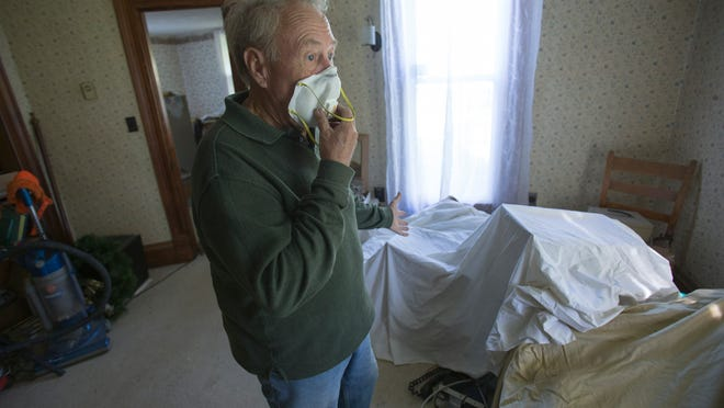 David Hale wears a protective mask inside his home that sits adjacent to the Bear Run Mine, operated by Peabody Energy, in Carlisle, Ind., Sept. 23, 2014. He says the dust comes from blasting at the nearby mine and has made it difficult to live inside the residence.