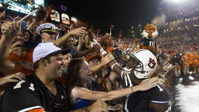 Auburn wide receiver D'haquille Williams celebrates with fans after the Tigers beat Arkansas 45-21 at Jordan-Hare Stadium on Saturday.
