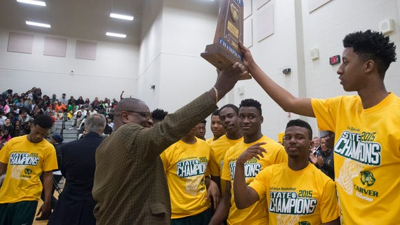 G.W. Carver's Carleton Williams receives the AHSAA Class 6A state championship trophy during Friday's presentation.