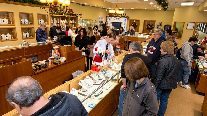 Park Place Jewelery owner Todd Ferrante, center, helps a customer with a sale in the Tangier Outlets in West Ocean City as others peruse the store.