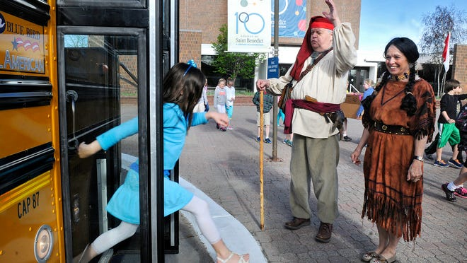 """John Augustin and Ellen Anderson greet students to the Young Authors Young Artists Conference in voyageur-era costumes at the College of St. Benedict Wednesday. The costumes reflected the """"Rendevous for Writers"""" theme at this year's event. Students in grades 3-6 from 48 schools will participate in the two-day event."""