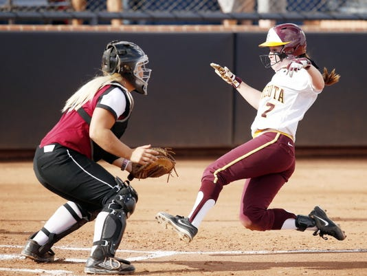 Minnesota's Sam Macken (7) scores in the first inning in front of New Mexico State catcher Tatum Reedy (9) during a Division I NCAA college softball game on Friday in Tucson, Ariz. (AP Photo/Rick Scuteri)