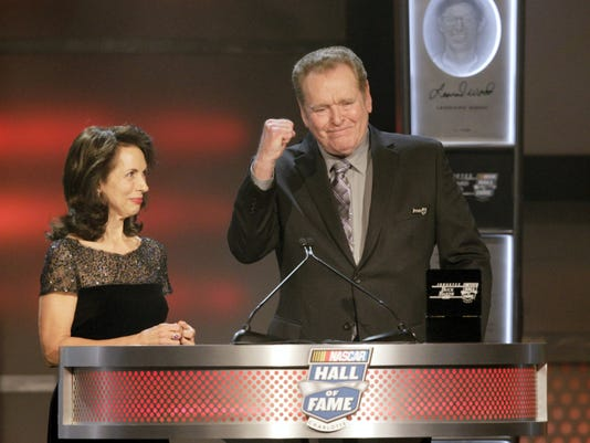 In this Feb. 8, 2013, file photo, Susan Baker, Buck Baker's widow, smiles as his son, Buddy Baker, pumps his fist during Buck Baker's induction at the NASCAR Hall of Fame in Charlotte, North Carolina. Buddy Baker, a former Daytona 500 winner and NASCAR Hall of Fame nominee, has died after a brief battle with lung cancer. Baker was 74.
