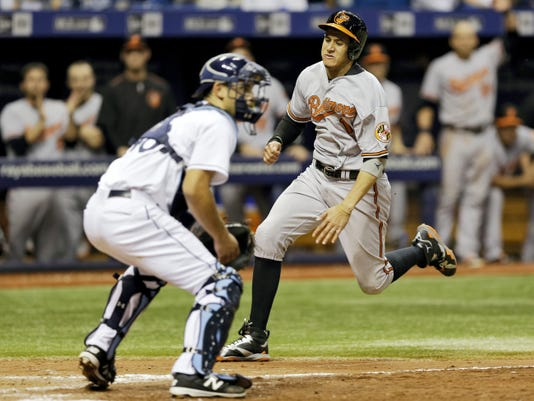 Baltimore's Manny Machado, right, races home ahead of the throw to Tampa Bay Rays catcher Luke Maile to score on a two-run single by Adam Jones during the eighth inning on Thursday in St. Petersburg, Fla.