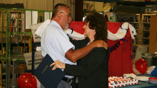 Yustin Riopko and Elmira Post Master Nancy Diello hug during a retirement party for Riopko Tuesday. Riopko is retiring Friday after 47 years of working for the federal government.
