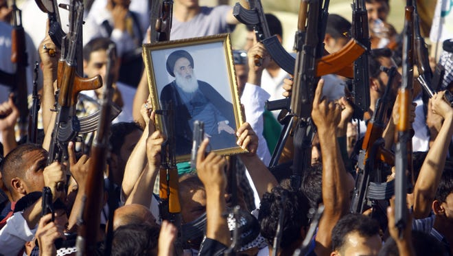 Iraqi Shiite tribesmen brandish their weapons and a poster of  Shiite cleric Grand Ayatollah Ali al-Sistani as they gather to show their willingness to join Iraqi security forces in the fight against Jihadist militants who have taken over several northern Iraqi cities, on June 17 2014, in the southern Shiite Muslim shrine city of Najaf. Airstrikes against ISIS militants began in Syria on Monday, September 22nd.