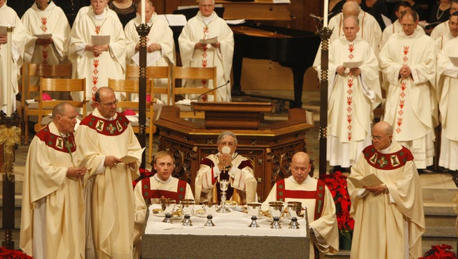 Bishop Salvatore Matano, bottom center, holds communion during the Mass of Installation.