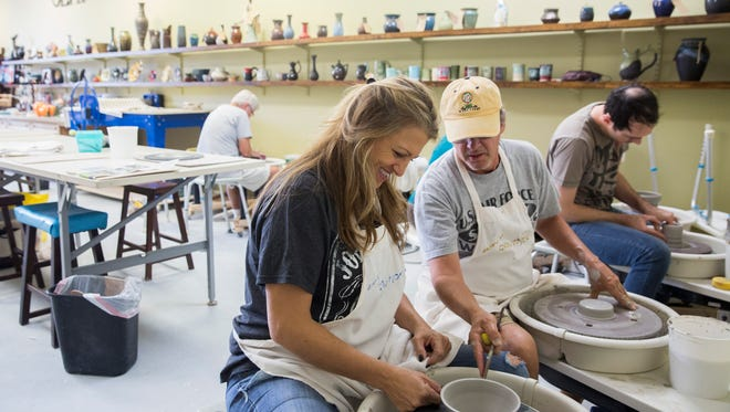 """Michelle Higgins, a relative newcomer to throwing clay, is given some pointers by Philip Stone, right, as the two, along with many others, help to throw as many bowls as possible during a bowl-throwing """"party"""" at Clay More Ceramics Sunday, Dec. 11, 2016 in Naples. All bowls created will be donated to the Empty Bowls: Naples charity event to be sold. All proceeds are then donated to the Harry Chapin Food Bank."""