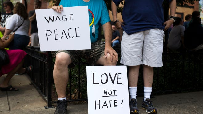 "Brian and Tammie Burroughs of Lenoir City hold signs during the Stand Against Hate rally in Market Square organized by the Women's March Coalition of East Tennessee in downtown Knoxville on Sunday, Aug. 13, 2017. The demonstration was in response to the ""Unite the Right"" rally a day earlier in Charlottesville, Va., which left three people dead."