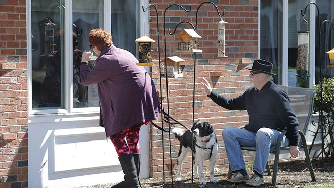 Brenda Burke, of Holbrook, and husband, Mike Flagg, with their dog, Casey, wave to her mom Mary, 91, at her window at Queen Anne Nursing Home on Sunday.