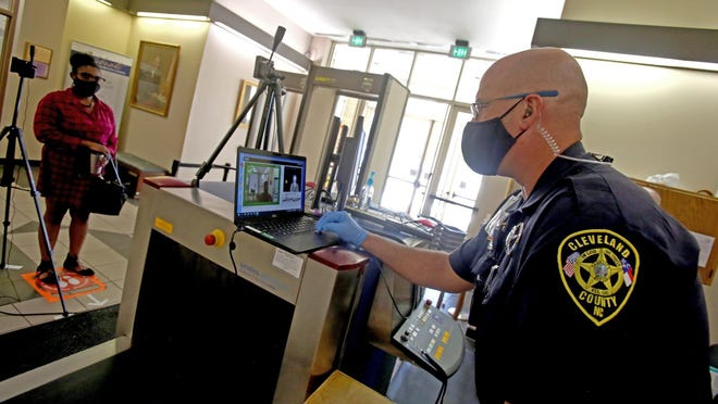 Deputy Paul Leigh uses a scanner to monitor the temperatures of visitors to the Cleveland County Courthouse.