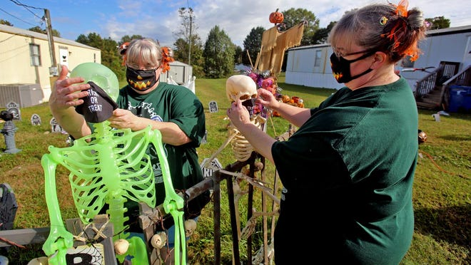 Tonie Ervin and Tonia Brown adjust masks on their skeletons at the Ghastly Manor. The haunt is located at 102 Exeter Lane in Shelby.
