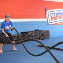 Tobi Soileau, general manager of Alexandria Fit Body Boot Camp, performs jumping jacks using battle ropes. The battle ropes can be used to work on the upper body, arms, legs and core depending on the exercise.