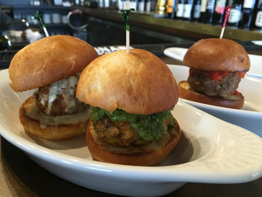 Veggie meatball  sliders with garlic cream sauce and spicy cilantro sauce at Mimi Blue. A beef meatball with marinara sauce is in the background.
