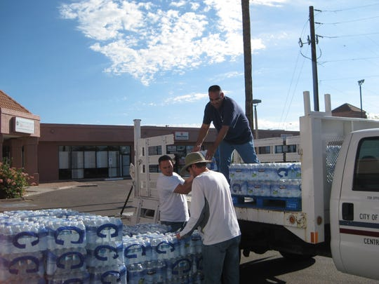 Chandler employees Jason Tiller (front left), Richard Toon (front right) and James Kame (standing in truck) unload cases of donated water at Matthew's Crossing Food Bank.