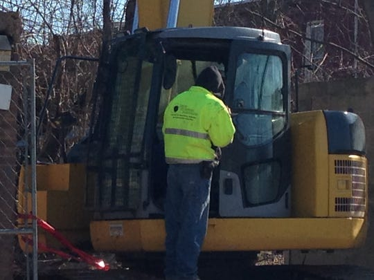 Workman cleaning up rubble at demolition site