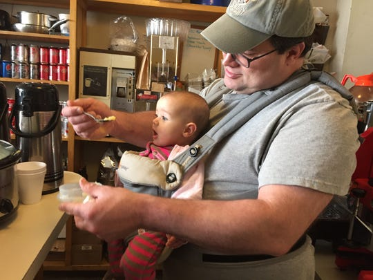 Restaurant owner Steve Trach feeds his seven-month-old