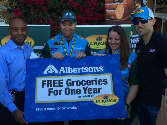 Danny Semerjibashian of Albertsons (left) and NASCAR driver Aric Almirola (right) surprised Phoenix's Cory and Laura Strouth with groceries for a year and an Alaskan cruise.