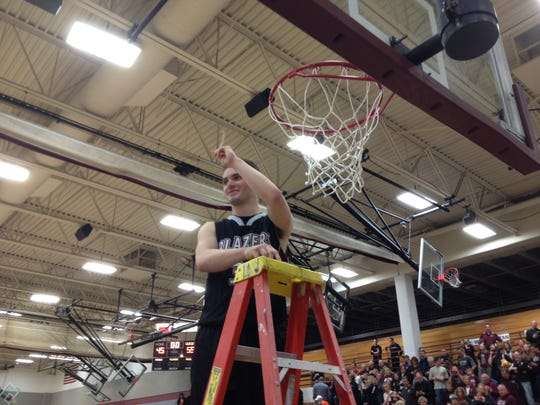 N.E.W. Lutheran senior Joey Siudzinski helps cut down the net following the Blazers' sectional championship.