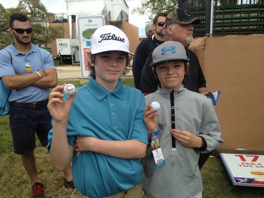 Two youngsters show off golf balls signed by Shreveport's