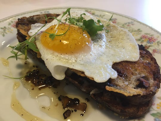 A fried duck egg crowns raclette  grilled cheese on cranberry walnut bread, all drizzled with black truffle honey at Milktooth.
