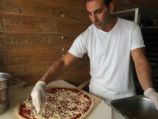 Vinny Tumminello spreads cheese across one of his pizzas