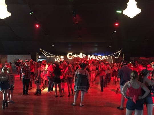 Festivalgoers do the Watermelon Crawl, a well-known line dance, in the Stagecoach Honkytonk on Friday.