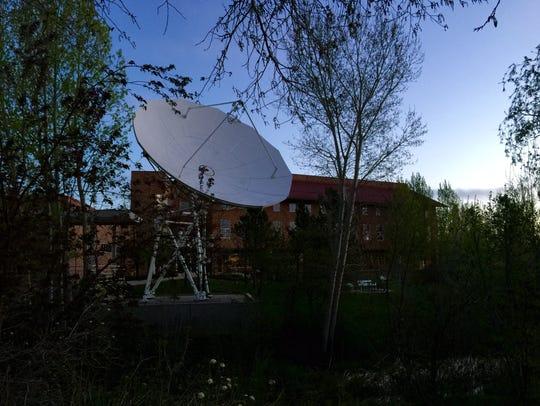A dish antenna points skyward in the pre-dawn light