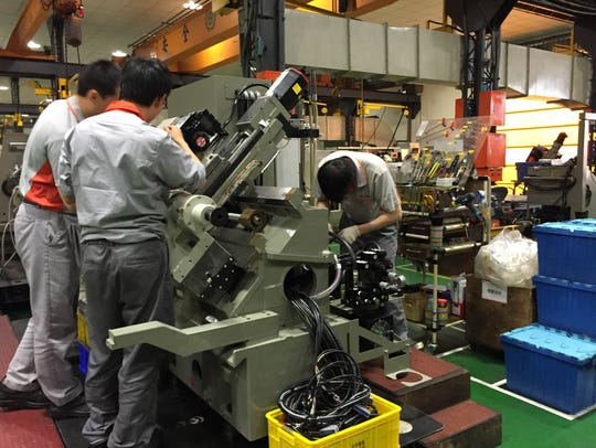 Workers calibrating a metal working machine at Victor