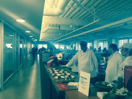 A chef from Bigalora Wood Fired Cucina prepares food at the opening of Commonwealth//McCann's new Detroit offices.