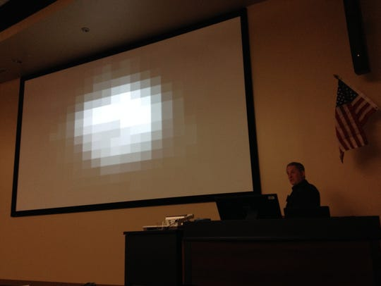 Dr. Alan Stern shows the audience a photo of Pluto,