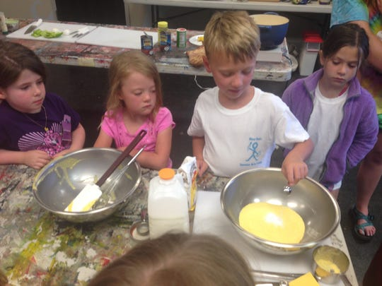 "Stirling Wallace (third from right, white shirt) measures and pours salt into a bowl of ingredients for cornbread during the culinary arts session of the River Oaks Square Art Center Summer Arts Studio on Monday. Fellow campers Claire Jackson, Susan Grace Clancy and Emma Shelette also got a turn helping with the recipe during the ""Taste of Louisiana"" session."
