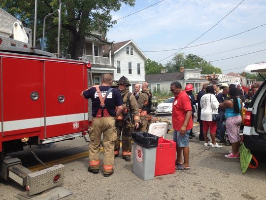 Salvation Army volunteer James Gardner supports the Cincinnati Fire Department at a three-alarm fire during a summer 2014 hot spell, serving cold water to rehydrate firefighters and victims.