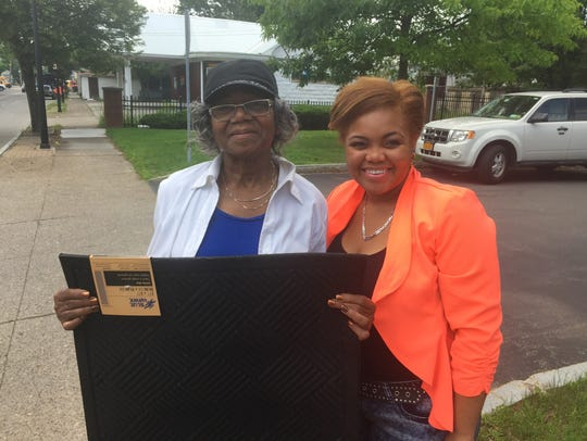 Annette McFarland, left, picks up a doormat meant to