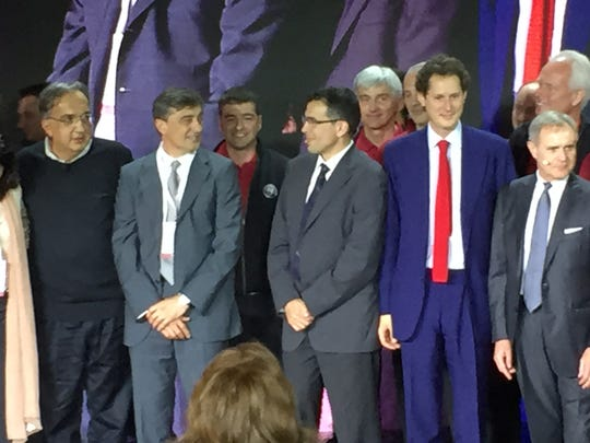 FCA CEO Sergio Marchionne, left; Phillippe Krief, third from left, FCA Chairman John Elkann and Alfa Romeo CEO Harald Wester stand on stage with several others to celebrate the reveal of the Alfa Romeo Giulia in Milan, Italy.
