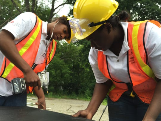 Detroiters Byron Kirk, 19, at left, and Ikesha Brooks, 21, prepare boards that will be used to secure windows at the vacant Holcomb Elementary School on Detroit's northwest side on Tuesday, June 30, 2015.