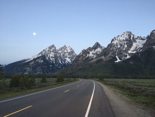 The moon shines over the mountains in Grand Teton National