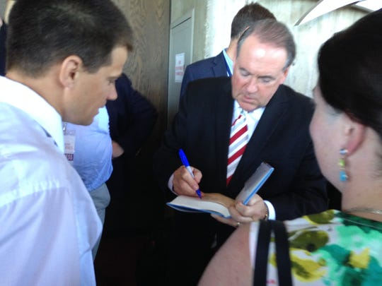Mike Huckabee signs at book at the Family Leadership Summit in Ames on July 18.