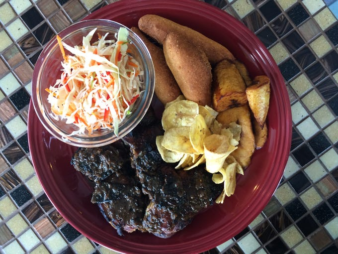 Jerk chicken is served with cole slaw, two kinds of