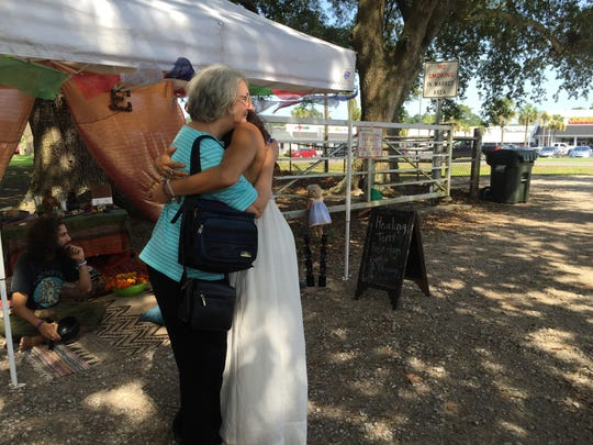 Melodie McMath (right) gives out a free hug at the Lafayette Farmers and Artisans Market Saturday morning.