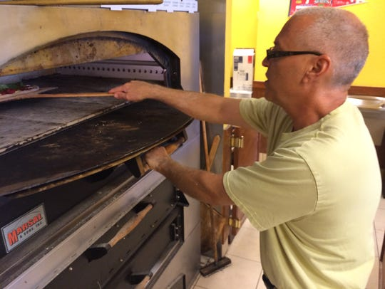 Owner Joe Calderone places a pizza into the 625-degree
