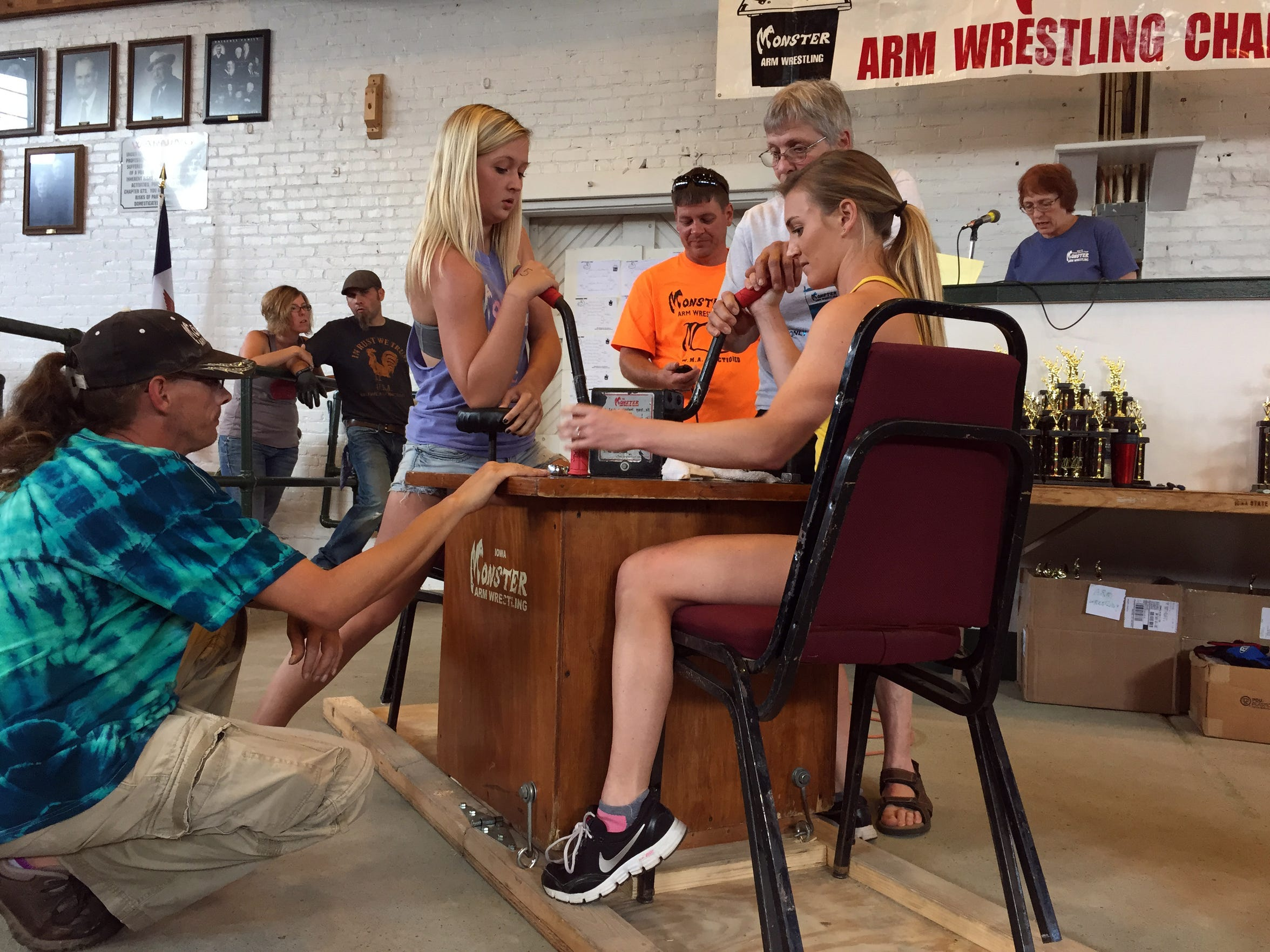 Laurisa Stringer, 20, standing, prepares for a match at the Monster Arm Wrestling Championships on Sunday, Aug. 16, 2015 at the Iowa State Fair.