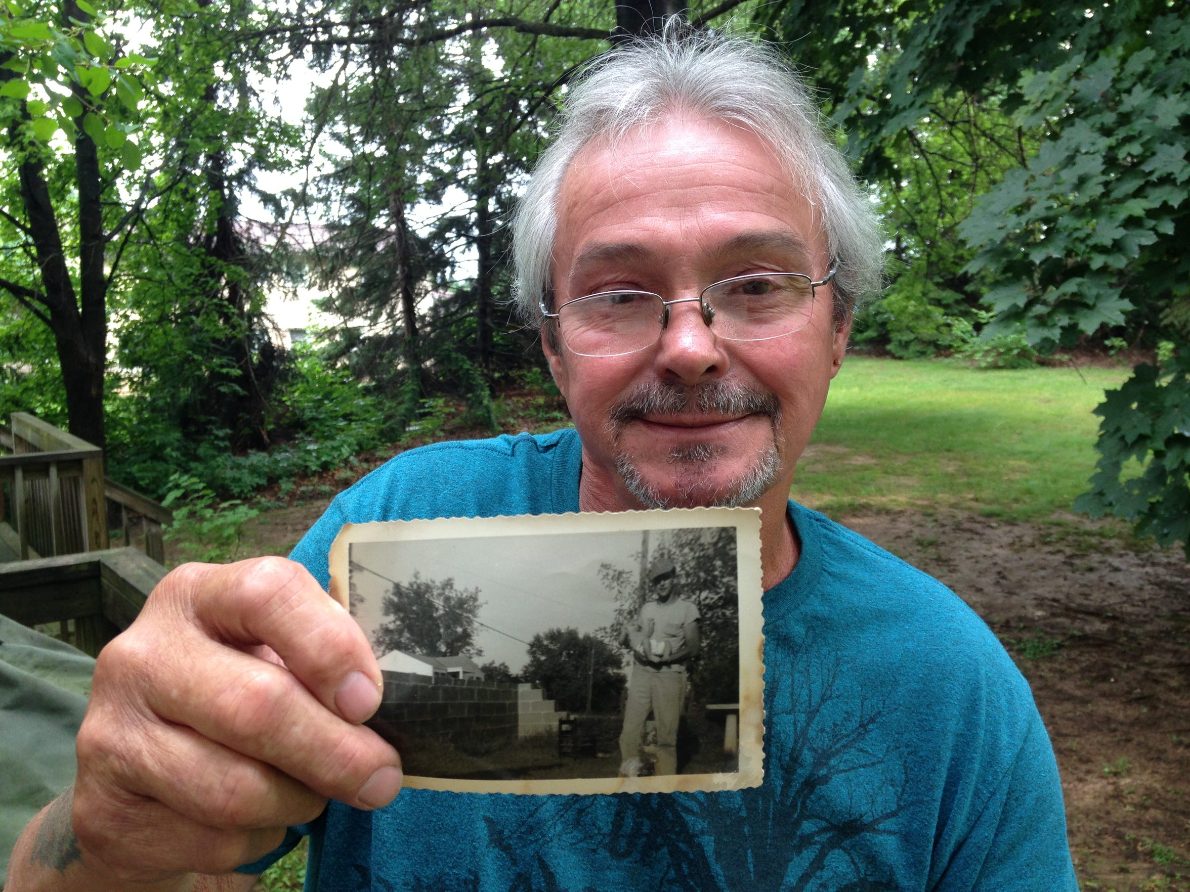 Richard Flynt holds a family photo of his late father, Eugene, on the back porch of his home in North Canton, Ohio.