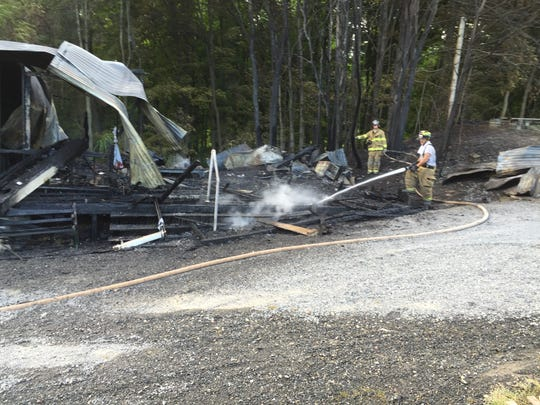 Firefighters extinguish a fire at the Rhinebeck Aerodome on Thursday.