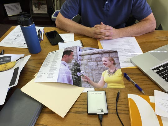 Brad Jenkins, general manager for The Breeze, James Madison University's student-run newspaper looks through brochures to find pictures of Alison Parker, a former staff member and JMU alum gunned down Wednesday morning on camera.