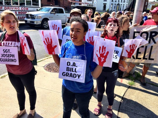 "Marchers hold up hands painted in ""blood"" red."
