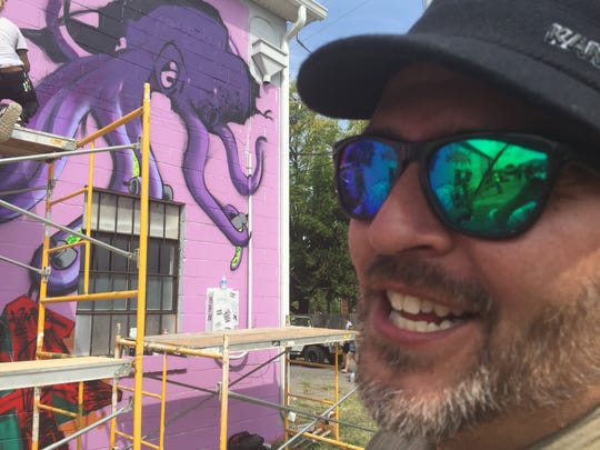 Artist Clinton Jones likes the way the south wall is coming along at Virginia Street Arts Festival Saturday in Waynesboro. The purple octopus in the background is his work.