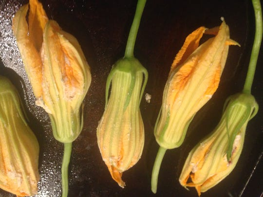 Delicate squash blossoms are stuffed with goat cheese, sun dried tomatoes and thyme. They can be eaten raw or slightly roasted.